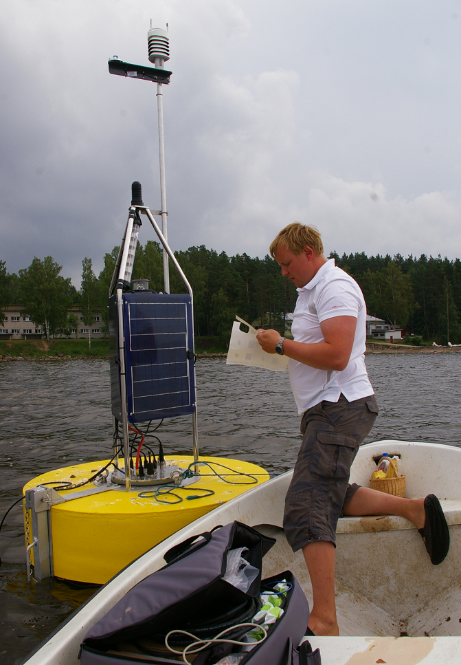 Alo Laas on the lake with a buoy that measures water parameters
